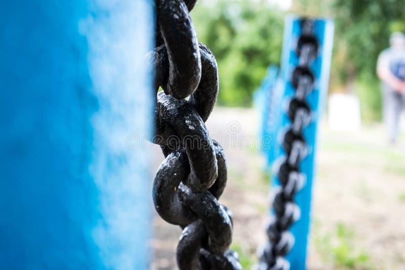 Stały i wielki metalu czerni łańcuch na ogrodzeniu z błękit drymbami, baza obrazy royalty free