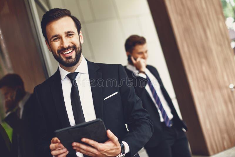 Stań w górze z młodym, eleganckim mężczyzną, stojącym z tabletem i kolegą, stojącym w pobliżu obrazy stock