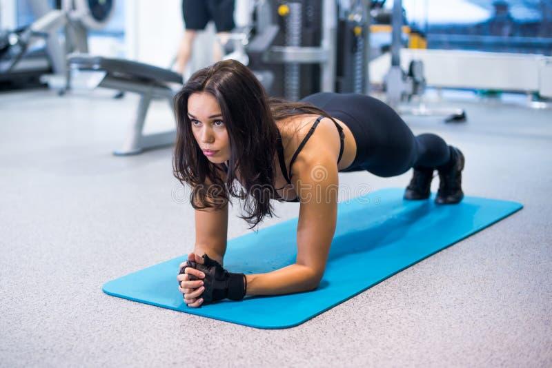 Stażowa sprawności fizycznej kobieta robi deski sedna ćwiczeniu obrazy royalty free
