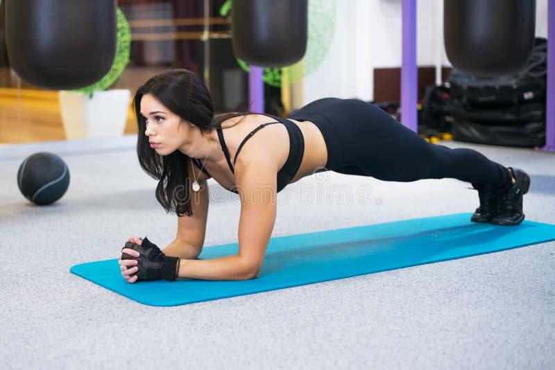 Stażowa sprawności fizycznej kobieta robi deski sedna ćwiczeniu pracującemu dla tylnych kręgosłupa i postury pojęcia pilates out  fotografia stock