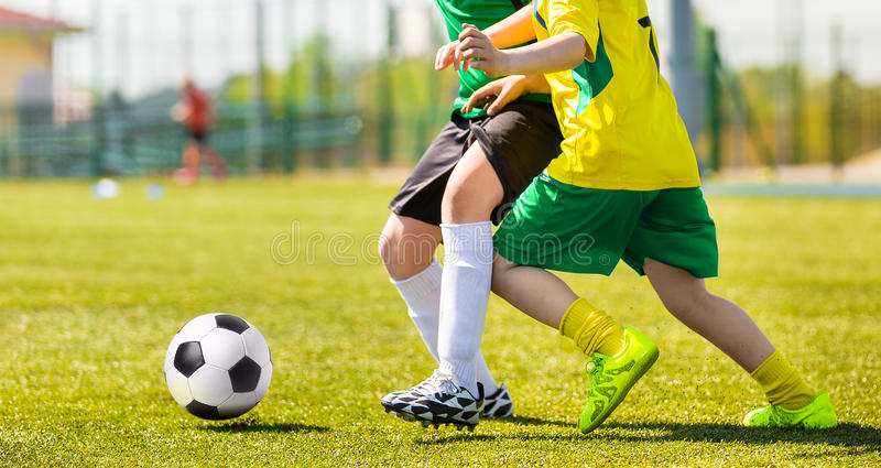 Stażowy i futbolowy dopasowanie między młodości piłki nożnej drużynami Młode chłopiec kopie mecz piłkarskiego obraz stock