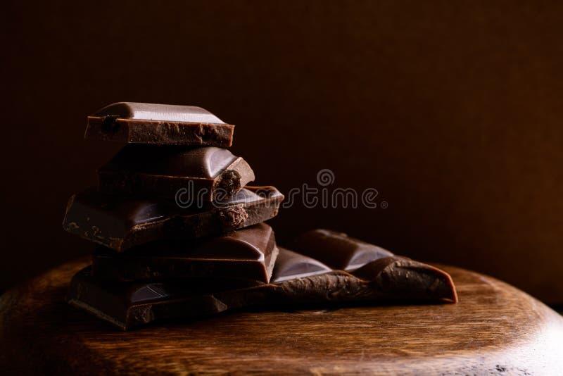 Staaf van donkere chocolade Gebroken stukken van chocolade op houten beer stock afbeelding