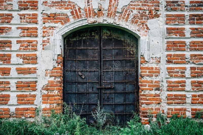 Staal roestige poorten of deur in rode bakstenen muur met gras bij geruïneerde oude kerk royalty-vrije stock foto