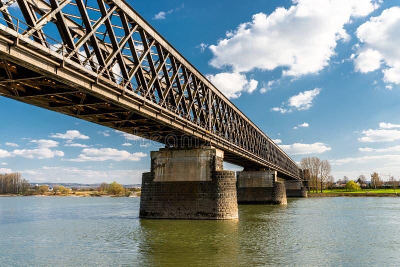 Staal, roosterstructuur van een spoorwegbrug over een rivier met een achtergrond van blauwe hemel met witte wolken in West-Duitsl royalty-vrije stock foto's