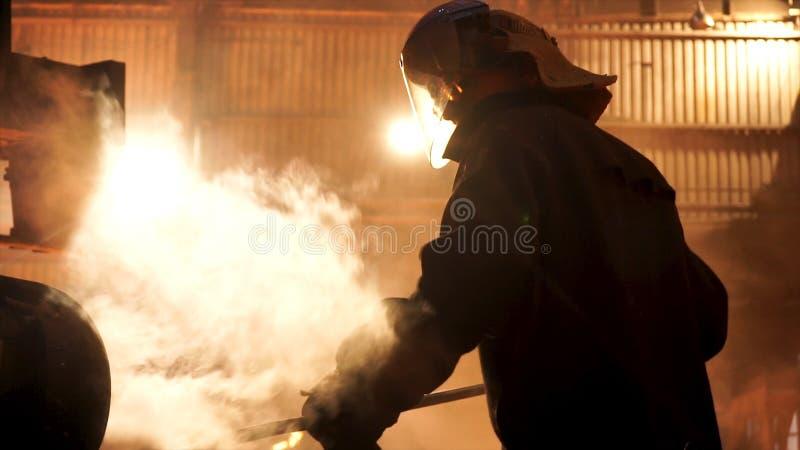 Staalarbeider die slakken uit de elektrische smeltende oven van de inductiesmeltkroes bij de metallurgische installatie, het hard stock afbeeldingen