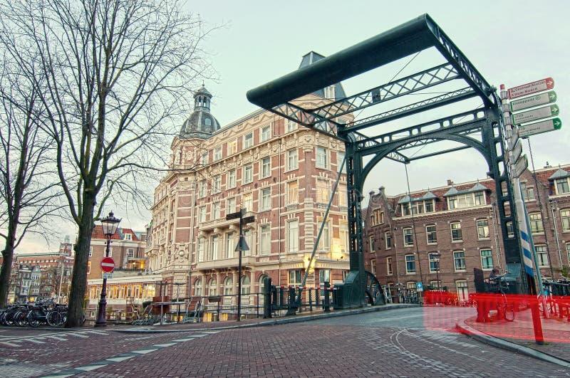 Staalstraat bro, järnelevatorbro på den Kloveniersburgwal kanalen i Amsterdam, Nederländerna, tidigt i vinter arkivbild
