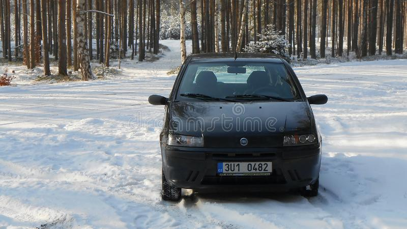 Staar Splavy, Tsjechische republiek - 09 December, 2012: zwarte auto Fiat Punto II dat op een sneeuw bosweg tijdens de wintertoer stock foto