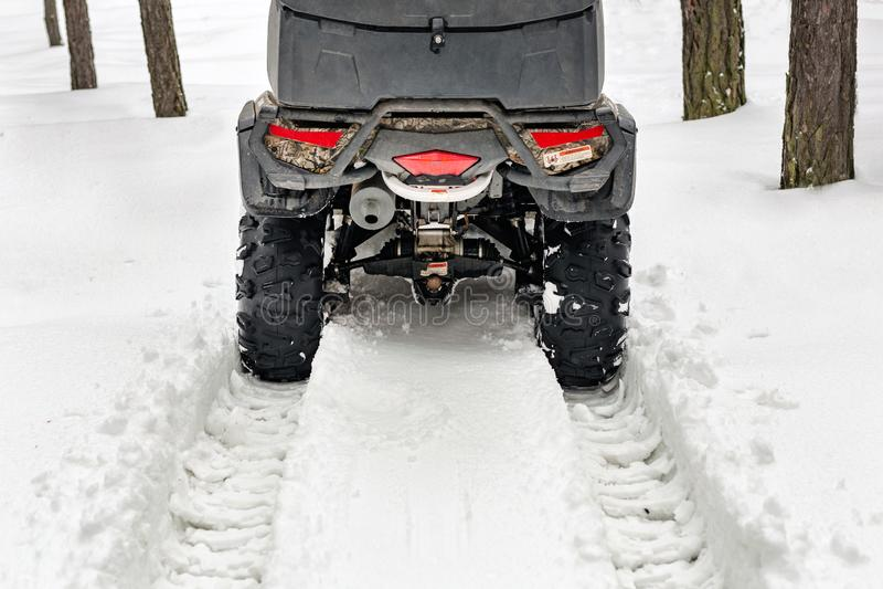 Staart van de vierlingfiets van ATV 4wd in bos bij de winter 4wd alle-terreain-helemaal voertuigtribune in zware sneeuw met diep  royalty-vrije stock fotografie