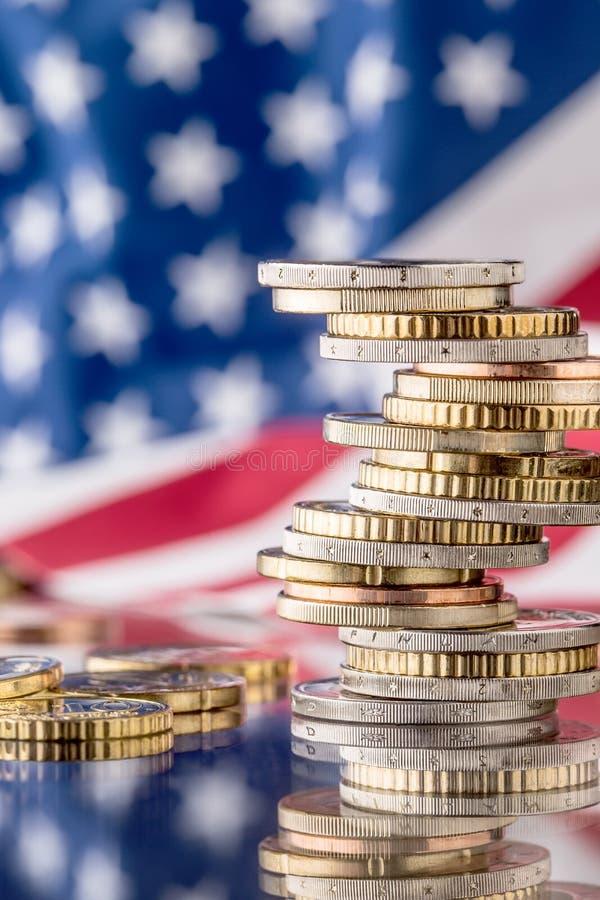 Staatsflagge von Amerika und von Euromünzen - Konzept Stapel der Euromünzen e lizenzfreies stockbild