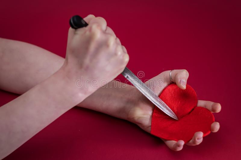 Valentines Day. Love heart. Breakheart. Female hand and pierces it heart knife. Stab the knife into the red heart in concept meaning Destroy my heart royalty free stock photos