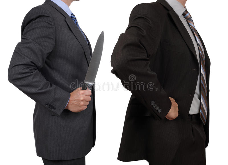Stabbed in the back. Concept conflict in the office one businessman holding a knife and stabbing another in the back royalty free stock photography