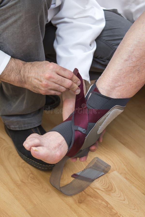 Stabilisateur de cheville placé sur la jambe de dame âgée photos stock