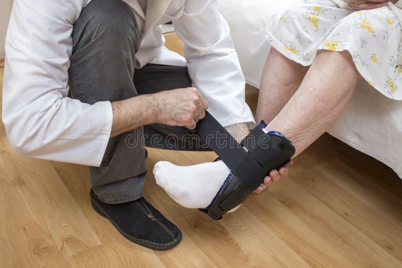 Stabilisateur de cheville placé sur la jambe de dame âgée photographie stock libre de droits