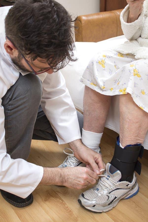 Stabilisateur de cheville placé sur la jambe de dame âgée Les tyes masculins d'infirmière la dentelle dans la chaussure de dame â photo libre de droits