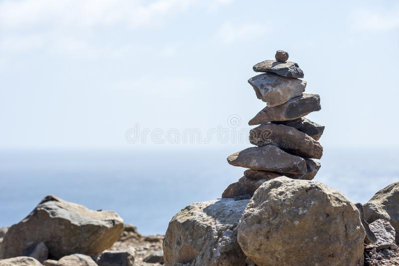 Stable stone on the island of Madeira. Stable stone tower by Ponta de São Lourenco on the island of Madeira with the Atlantic sea in the background stock image