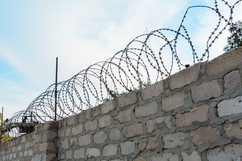 Stacheldraht auf Backsteinmauer oder Zaun vor blauem Himmel Konzept der Sicherheit und des Safes oder Beschränkung der Freiheit u stockbilder