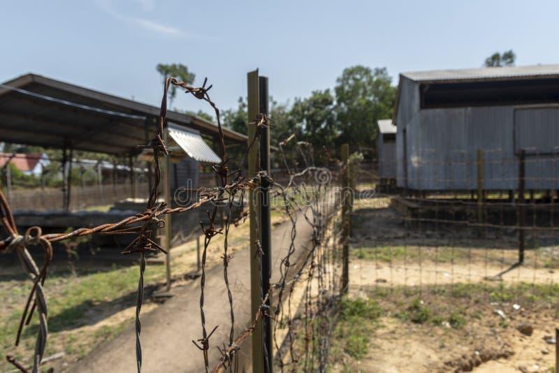 Stacheldraht mit Gefängniskasernen im Hintergrund, von Gefängnis Phu Quoc, Vietnam lizenzfreie stockbilder