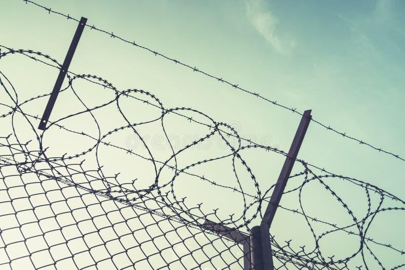 Stacheldrahtstahlwand gegen immigations Wand mit Stacheldraht auf Grenze von 2 Ländern Private oder geschlossene Militärzone lizenzfreies stockbild
