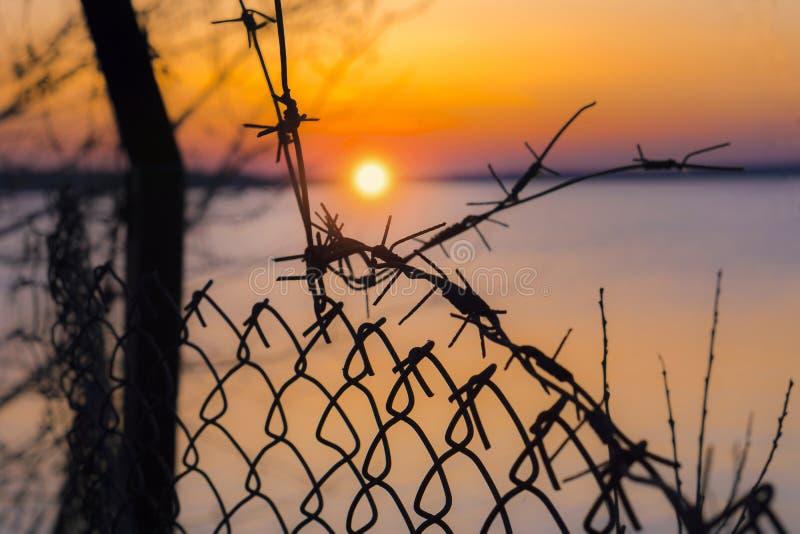 Stacheldrahtzaun über Hintergrund des schönen Sonnenuntergangs auf See lizenzfreie stockfotos