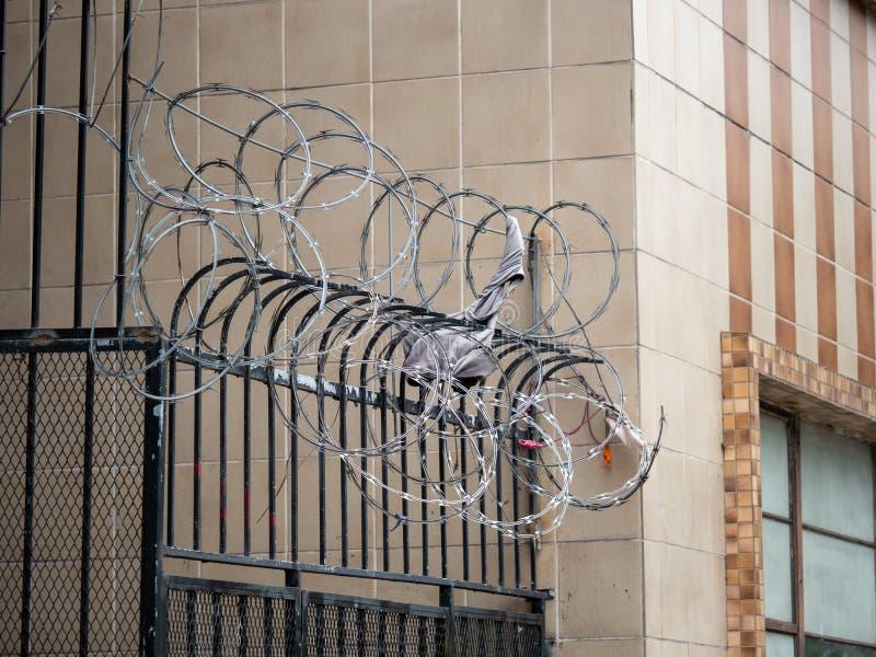 Stachelrasiermesserdraht über schwarzem Zaun mit den Einzelteilen nach innen gehaftet stockfotografie