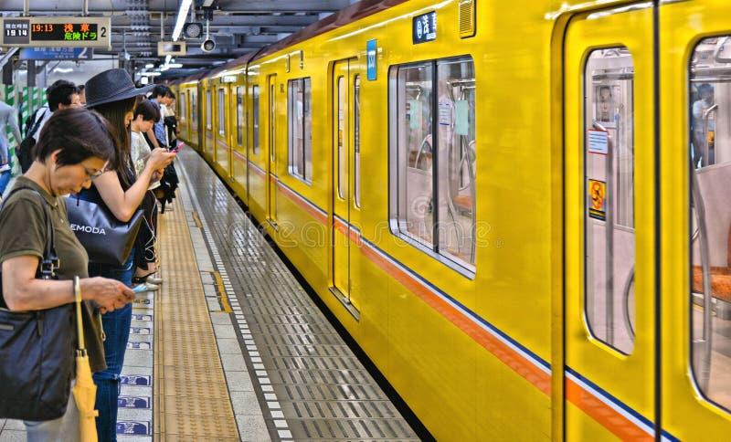 Stacja metra z kolor żółty taborową i nowożytną architekturą z ludźmi czekać na taborową przerwę w Tokio metrze, Japonia zdjęcie stock