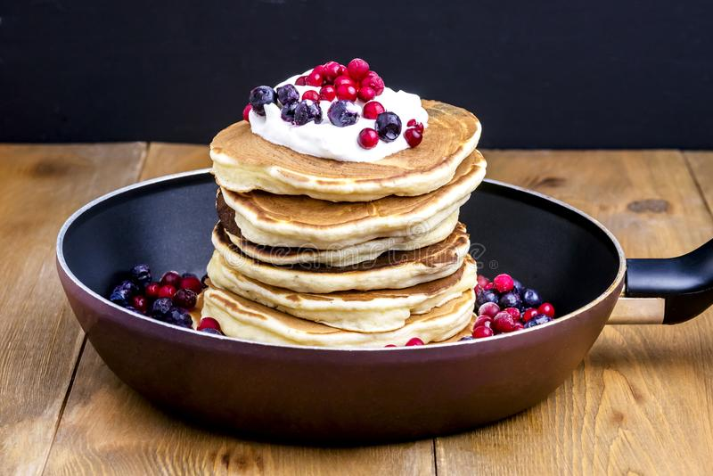 Stack of American Pancakes with Cranberry and Blueberry on Pan Wooden Rustic Background Tasty Breakfast royalty free stock photo