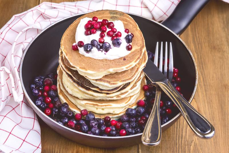 Stack of American Pancakes with Cranberry and Blueberry on Pan Wooden Rustic Background Tasty Breakfast Toned royalty free stock photography