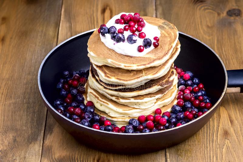 Stack of American Pancakes with Cranberry and Blueberry on Pan Wooden Rustic Background Tasty Breakfast stock image