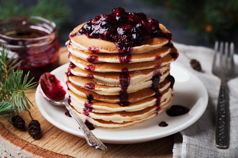 Stack of american pancakes or fritters with strawberry and blueberry jam in white plate on wooden rustic table decorated Christmas stock photos