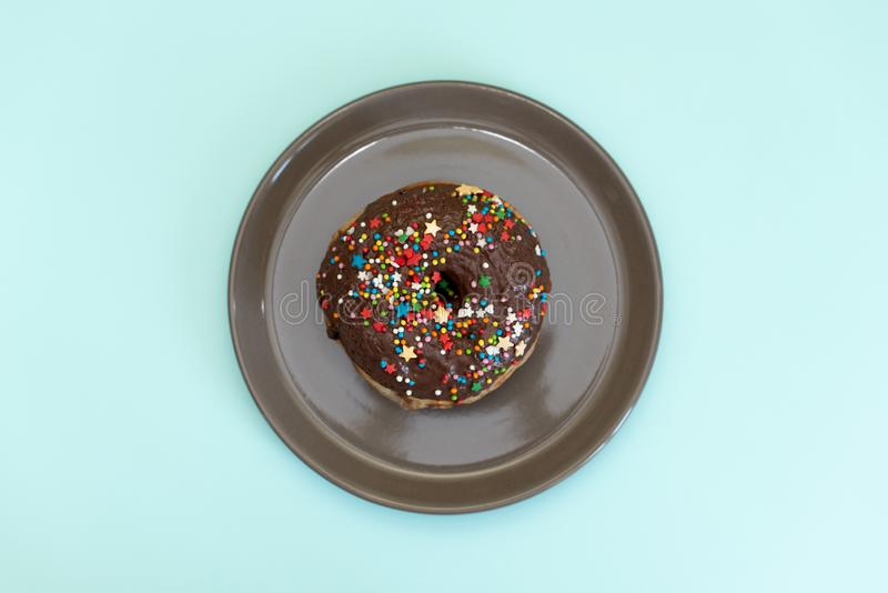 Stack of assorted donuts on black and blue cement background. Blue glazed doughnut with sprinkles on foreground. Copy space. royalty free stock photos
