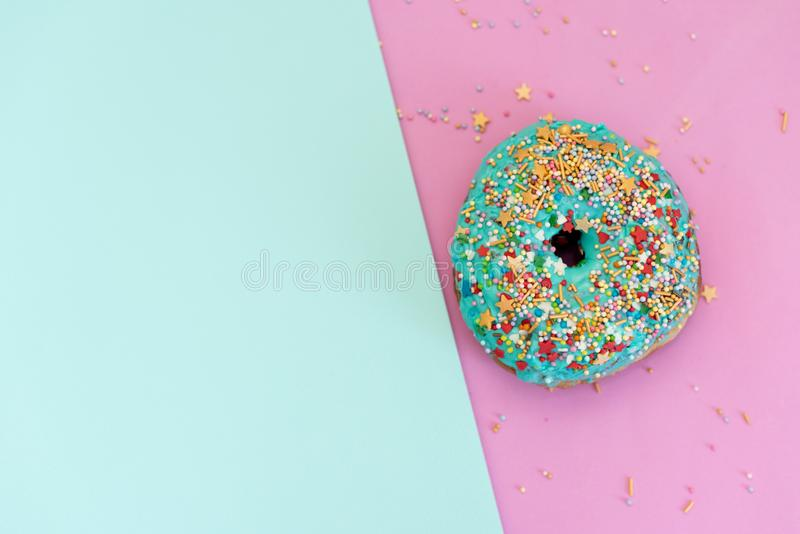 Stack of assorted donuts on black and blue cement background. Blue glazed doughnut with sprinkles on foreground. Copy space. stock images