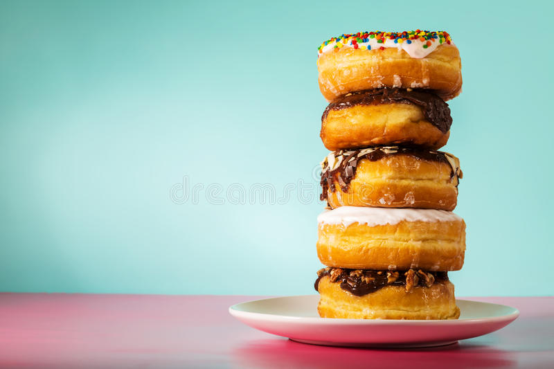 Stack of assorted donuts on pastel blue and pink background royalty free stock photos