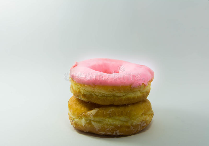 Stack of assorted donuts on a white plate on pastel royalty free stock images