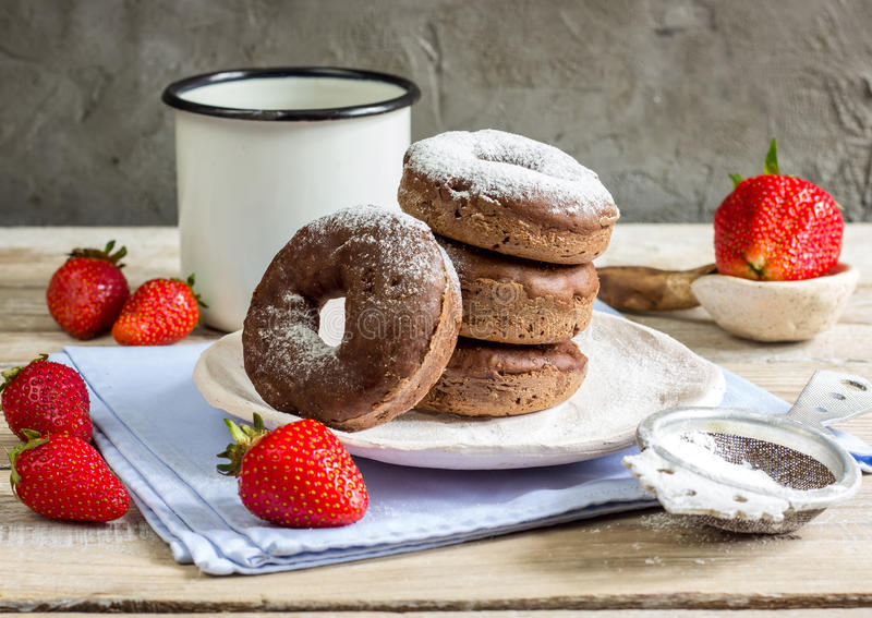 Stack of assorted donuts. On a white plate on on wooden rustic background royalty free stock photography