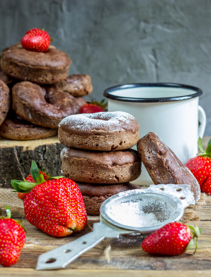 Stack of assorted donuts. On a white plate on on wooden rustic background stock images
