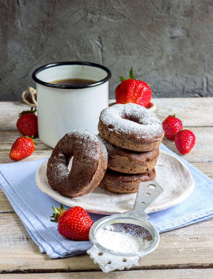 Stack of assorted donuts. On a white plate on on wooden rustic background stock photo