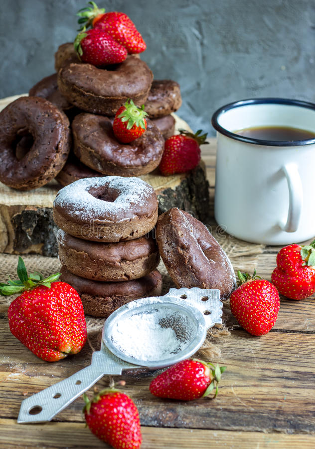 Stack of assorted donuts. On a white plate on on wooden rustic background royalty free stock photo