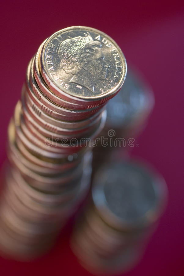 Stack of australian dollar coins. A large stack of australian dollar coins on a red background stock photo
