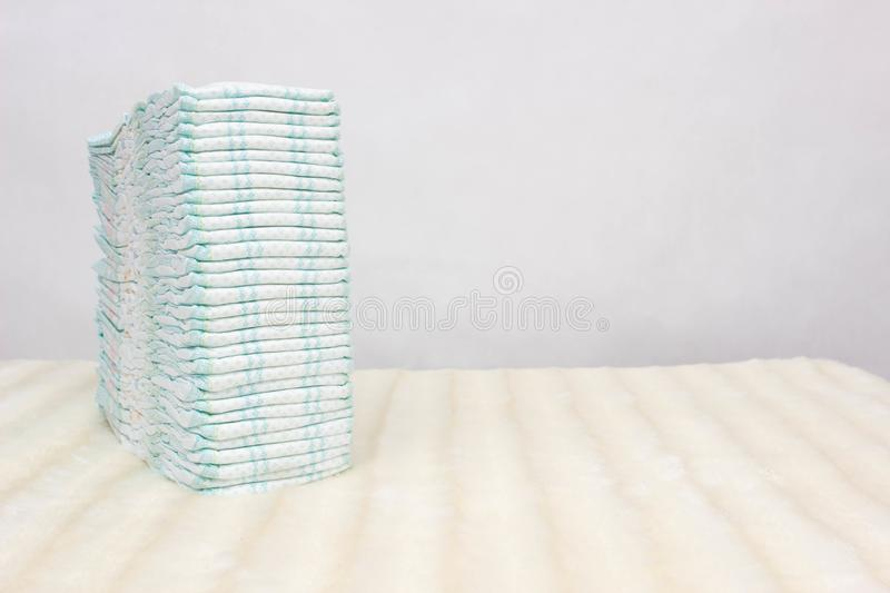 A stack of baby diapers on a white background, protection against leakage, dryness and comfort, hypoallergenic, copy space. Hygienics royalty free stock photo
