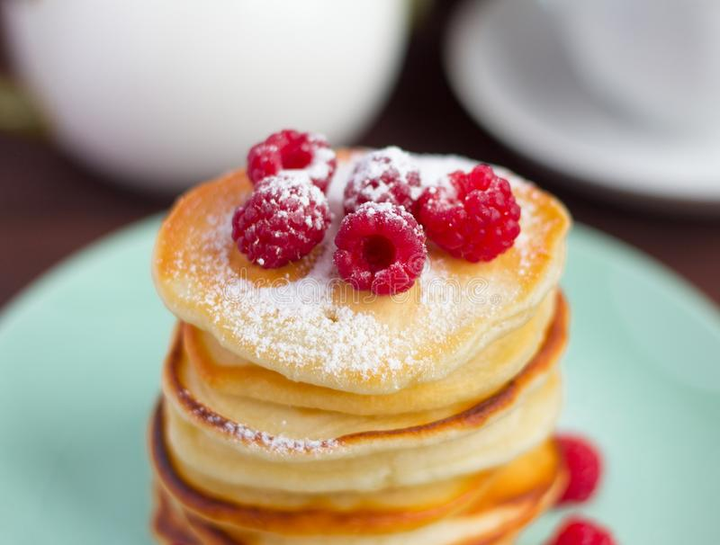 Stack of baked homemade pancakes with raspberries, sprinkled with powdered sugar and tea utensils in the background, selective royalty free stock photography