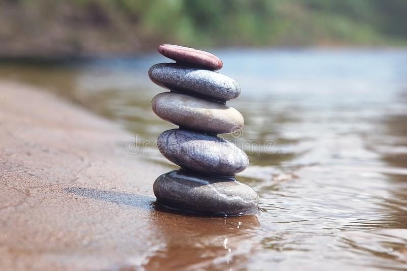 Stack of balancing pebble stones on sand and water edge as zen symbol royalty free stock images