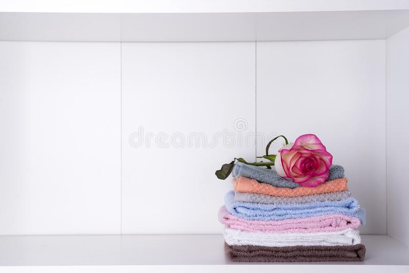 Stack of bath towels with rose on light background royalty free stock photography