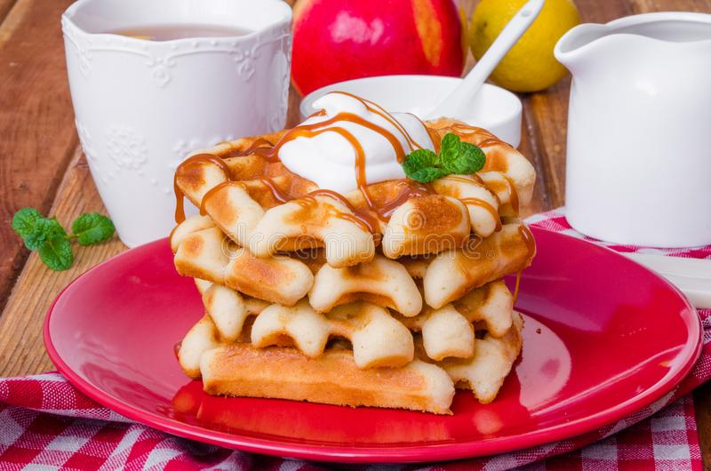 Stack Belgian waffles with caramel sauce and whipped cream on a plate. stock photography