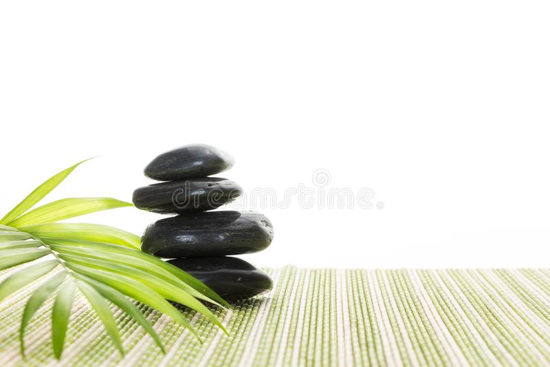 Stack of black basalt balancing stones with green leaf on bamboo mat, on white background. Stack of black basalt balancing stones with green leaf on bamboo mat royalty free stock photos