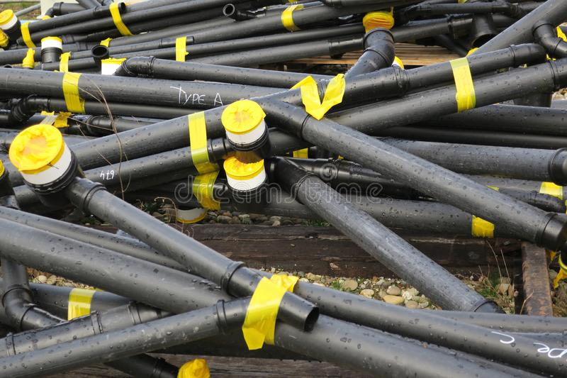 Stack of black pipe tubes hold together with yellow tape stock photos