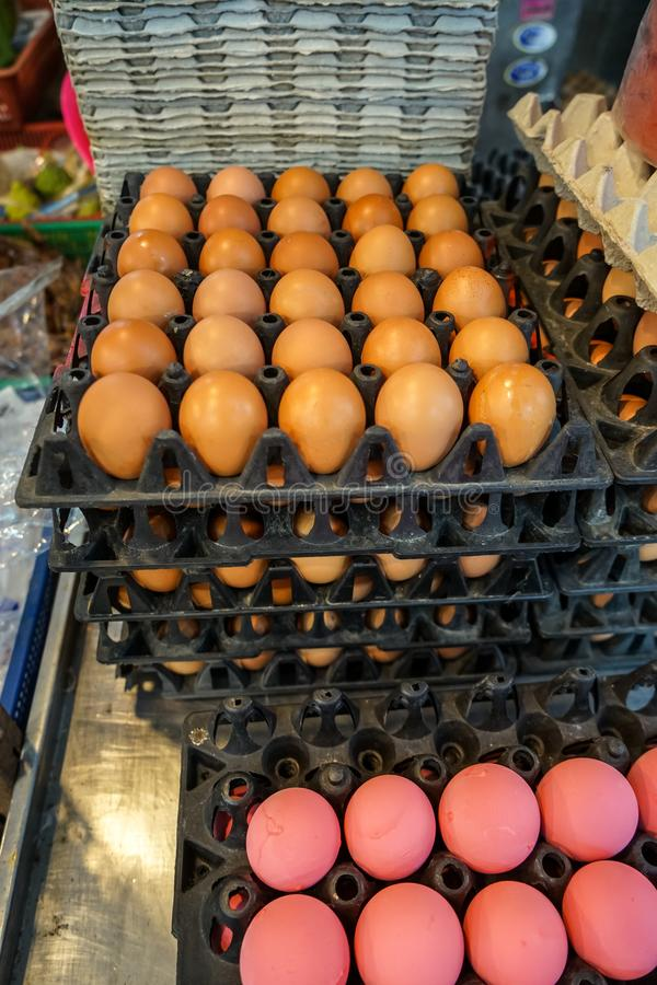 Stack of black trays full of natural light brown chicken eggs and pink preserved eggs selling in local food market royalty free stock photos