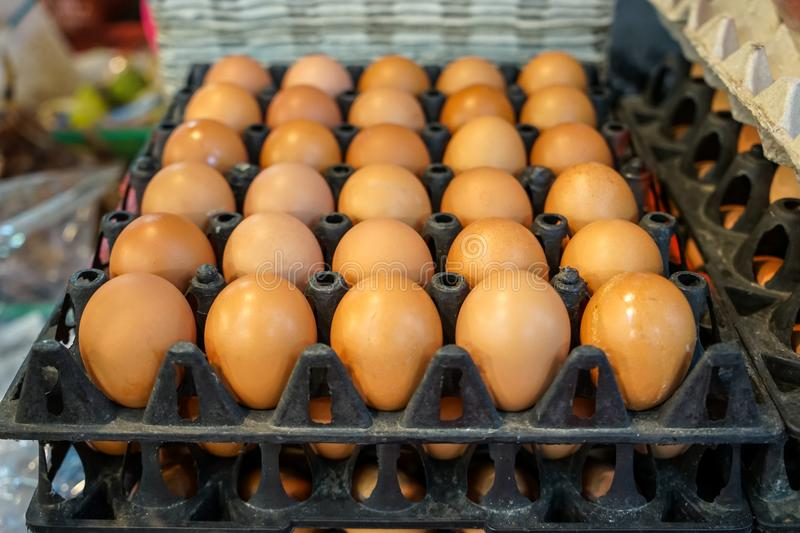 Stack of black trays and paper boxes full of natural light brown chicken eggs selling in local food market, selective focus stock photo