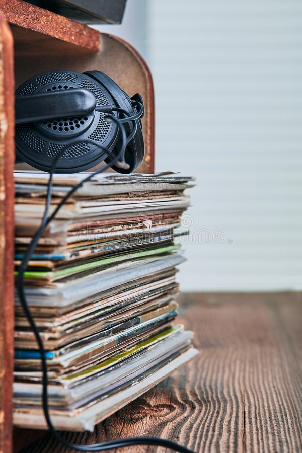 Stack of black vinyl records. And headphones on the top. Candid people, real moments, authentic situations royalty free stock photo