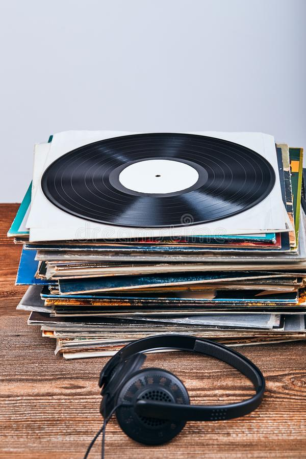 Stack of black vinyl records. And headphones on the top. Candid people, real moments, authentic situations royalty free stock image