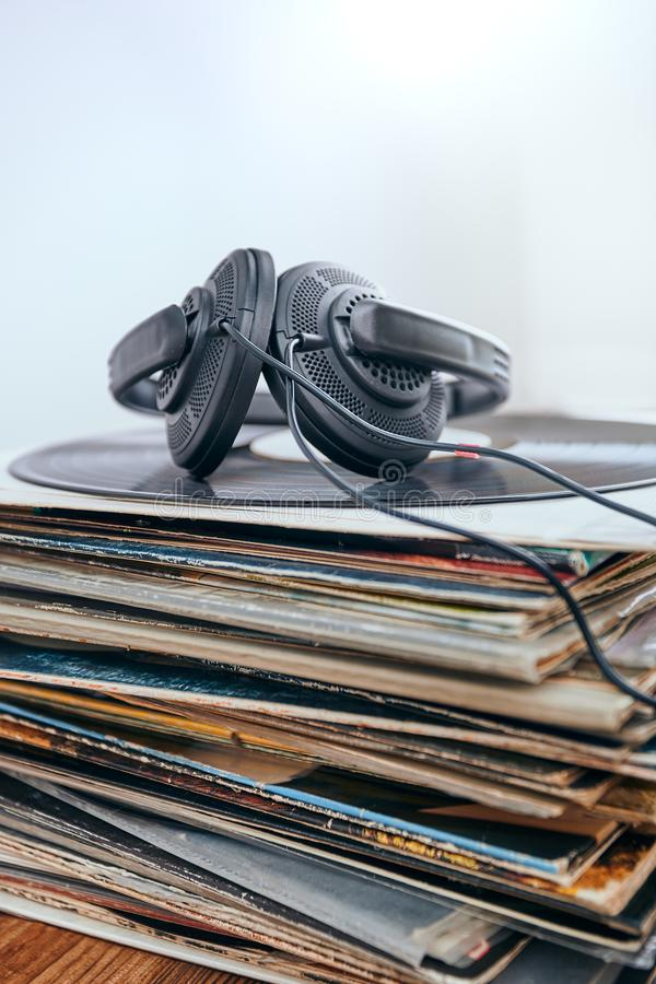 Stack of black vinyl records. And headphones on the top of stack. Candid people, real moments, authentic situations stock photography